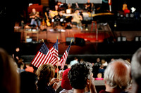 "A mother and son wave flags before a live broadcast of ""A Prairie Home Companion"" at Wolf Trap on May 28, 2011. The performance was on Memorial Day weekend."
