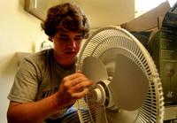 In his sister Nicki's room in Barrett Hall, Sam Purcell assembles a fan during freshmen move-in day on August 20, 2010.  Barrett and Monroe Halls on Old Campus do not have air conditioning, so many st