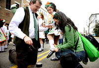 Naomi Cummings, right, unwraps daughter Kaeya Cummings' shoes so Peter Marsh, left, can attach duct tape to the bottom to improve traction before the 30th annual St. Patrick's Day parade in Old Town A