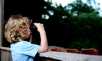 "A child uses binoculars to watch the stage before a live broadcast of ""A Prairie Home Companion"" at Wolf Trap on May 28, 2011."
