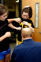 Senior Kate Hrdina, left, helps junior Caroline Sovick while Mike Pierson measures her for a uniform.[rehearsal7]